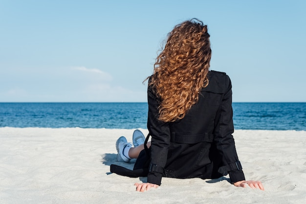 Girl with beautiful curly hair sitting on the beach in a coat and looking at the sea Premium Photo