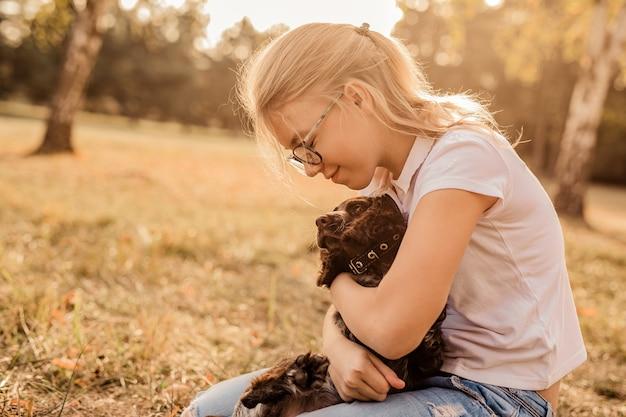 笑って小さな子犬と遊ぶ大きな眼鏡の女の子 Premium写真