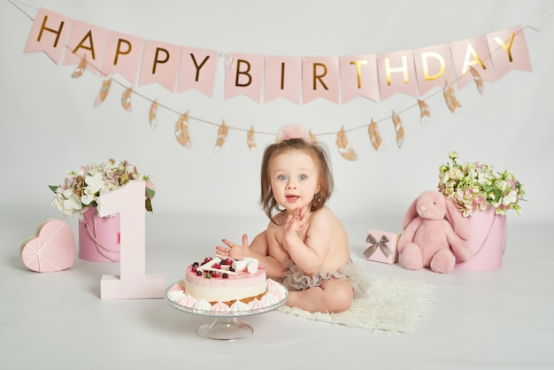Girl with a birthday cake, 1 year old baby photo session Premium Photo