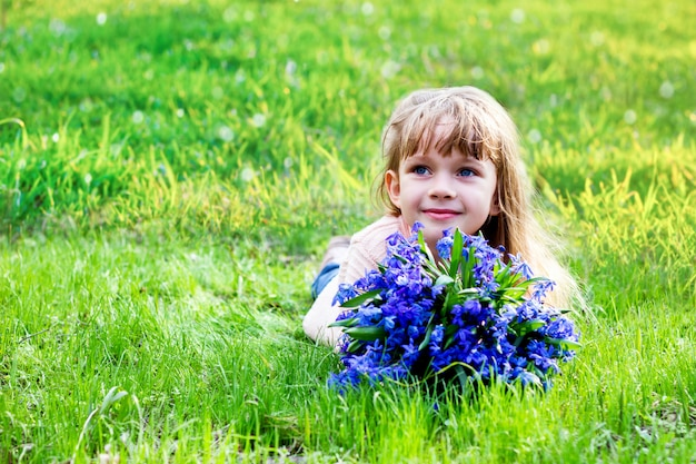 Girl with a bouquet of spring flowers on the green grass Premium Photo