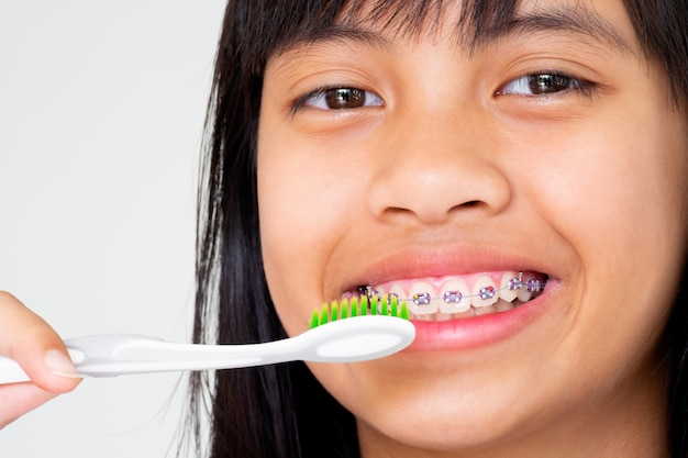 Girl with braces teeth hand holding toothbrush smiling and happy Premium Photo