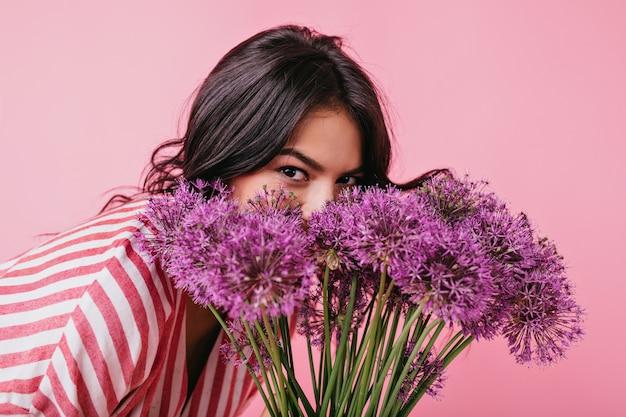 Девушка с карими глазами прячется за большими фиолетовыми цветами. портрет дамы с удовольствием. Бесплатные Фотографии