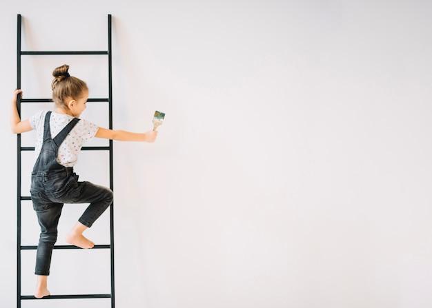 壁の近くの梯子の上のブラシを持つ少女 Premium写真