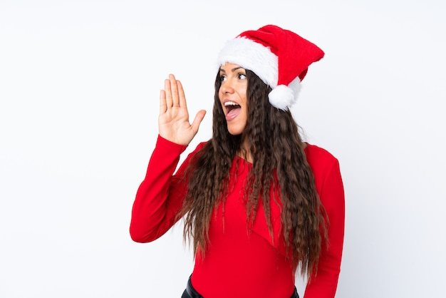 Girl with christmas hat over isolated white shouting with mouth wide open Premium Photo