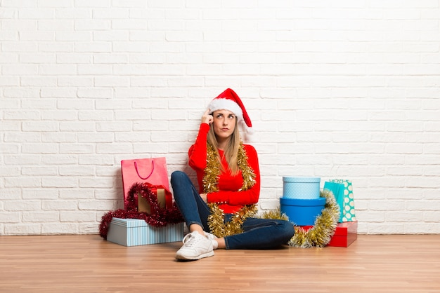 Girl with christmas hat and many gifts celebrating the christmas holidays standing and thi Premium Photo