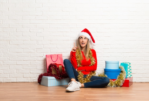 Girl with christmas hat and many gifts celebrating the christmas holidays standing Premium Photo