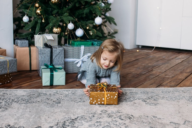 Girl with christmas present, christmas tree Premium Photo