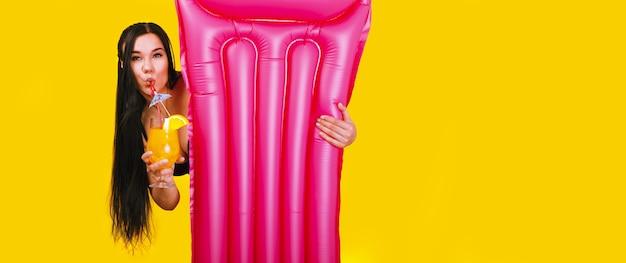 黄色の空間にカクテルと水泳マットレスを持つ少女 Premium写真