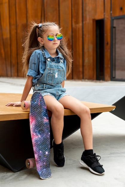 Girl with colorful skateboard and sunglasses Free Photo