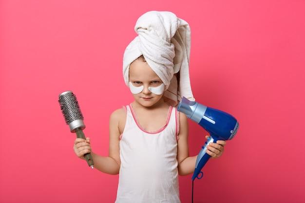 恥ずかしがり屋の表情でカメラを直接見ている櫛と髪の毛が乾いた女の子 Premium写真