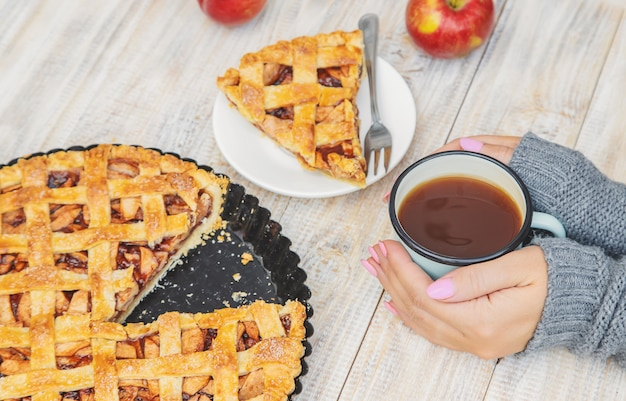 Girl with a cup of tea and a pie with apples and cinnamon. Premium Photo
