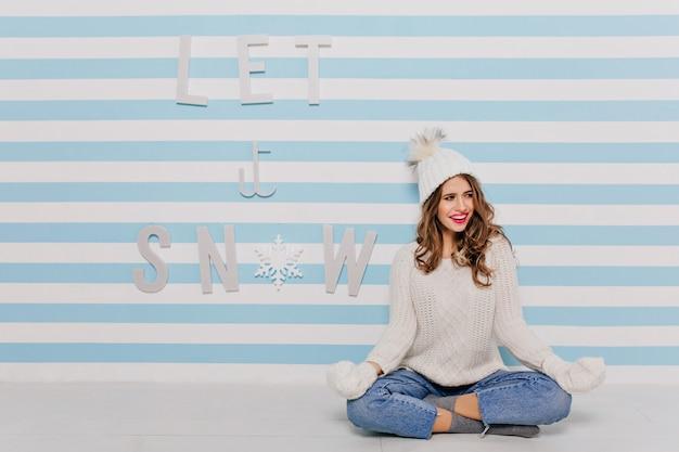 床で瞑想し、笑顔で目をそらしているカールを持つ少女。白と青の縞模様の壁のフルレングスの肖像画 無料写真