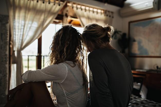 흰 블라우스를 입은 곱슬 빨간 머리를 가진 소녀는 집에서 그녀의 남자와 쉬고있다 무료 사진