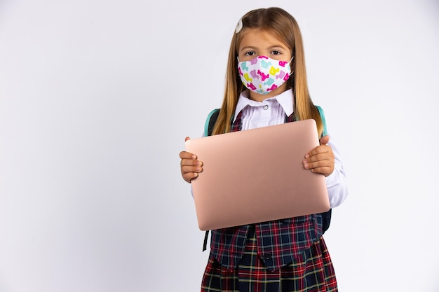 Premium Photo | Girl with custom face mask going back to school after  covid-19 quarantine and lockdown.school form and laptop in hand.