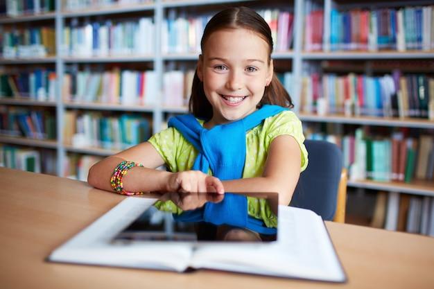 Girl with digital tablet in library Free Photo