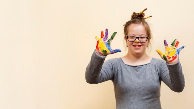 カラフルな手のひらを披露してダウン症候群を持つ少女 無料写真