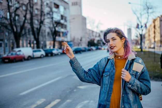 Girl with dyed hair hailing a cab. Premium Photo