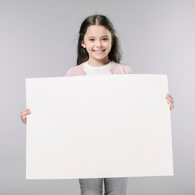 Girl with empty poster in studio Free Photo
