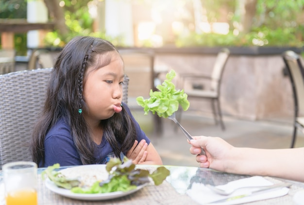 Girl with expression of disgust against vegetables Premium Photo