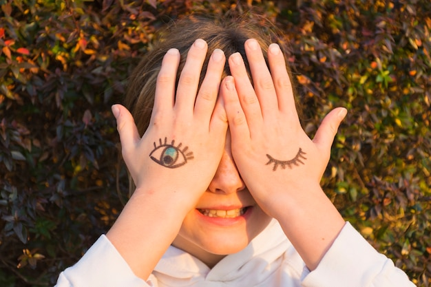 Girl with eye tattoos on hand palm covering her eyes Free Photo