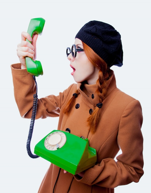 Girl with eyeglasses and coat talking by phone Premium Photo