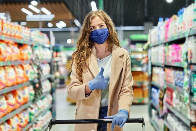 フェイスマスクを持った女の子は、パンデミックの際に親指を立ててスーパーマーケットで食料品を購入します。 Premium写真