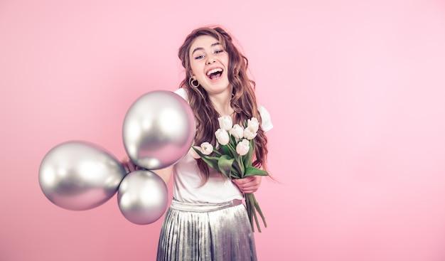 Девушка с цветами и воздушными шарами на цветной стене Бесплатные Фотографии