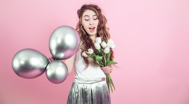 花と色の背景上のボールを持つ少女 無料写真