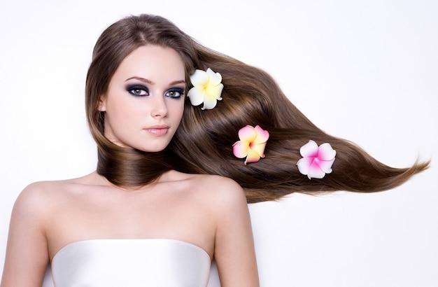 Ragazza con fiori nei suoi bei capelli lisci e lunghi lucidi Foto Gratuite