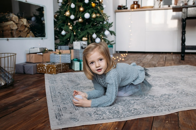 Girl with gift boxes and christmas tree on background Premium Photo