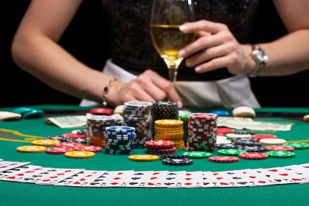 Premium Photo | A girl with a glass of wine playing poker