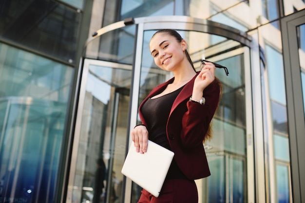 Girl with glasses on the background of a glass office building Premium Photo