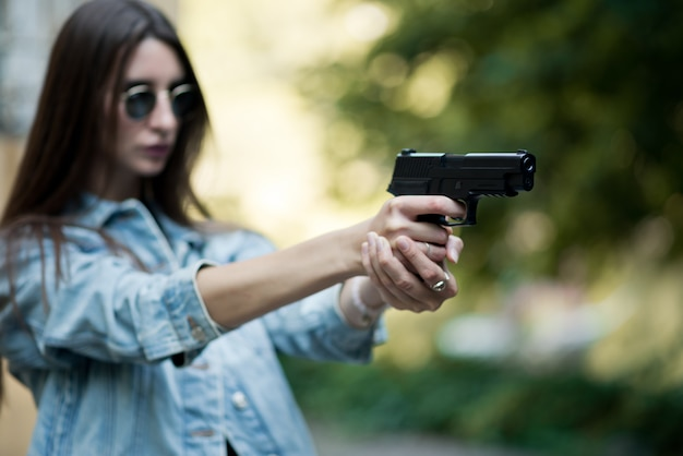 Girl with a gun on the street learns to shoot Premium Photo