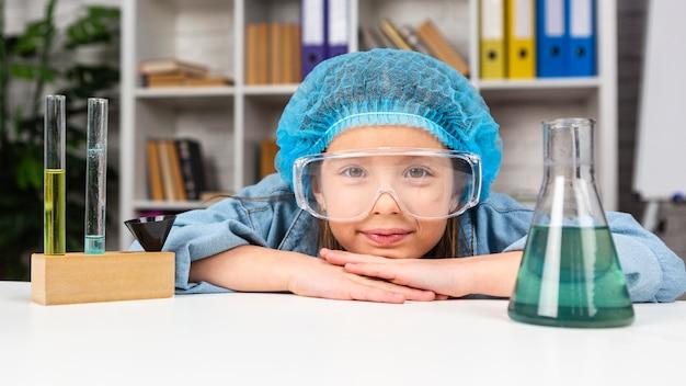 테스트 튜브로 과학 실험을하는 머리 그물과 안전 안경 소녀 무료 사진
