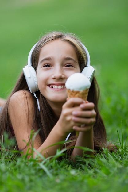 Ragazza con le cuffie che mangia il gelato Foto Gratuite