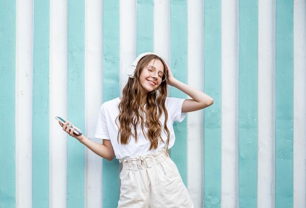 音楽を楽しむヘッドフォンを持つ少女 無料写真