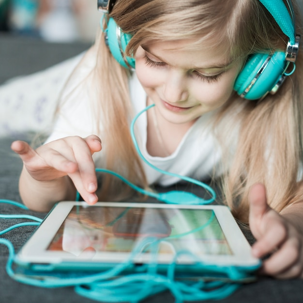 Girl with headphones touching tablet Free Photo