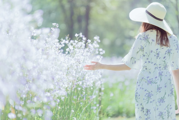 Girl with her back and  straw hat  in a field of flowers, happy asian woman Premium Photo