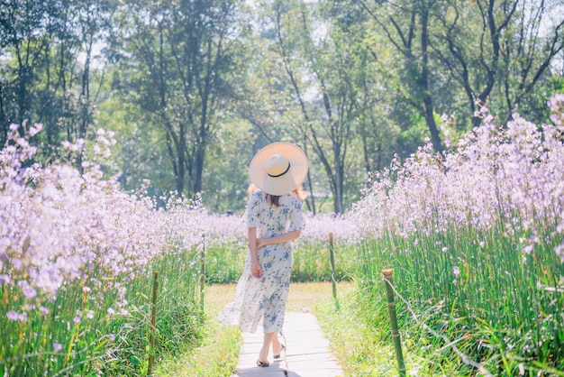 Girl with her back and  straw hat  in a field of flowers Premium Photo