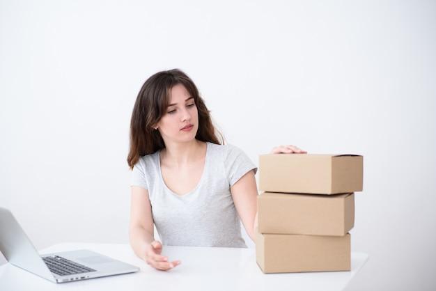 彼女の髪の少女、ラップトップに座って段ボール箱のスタックを見ている灰色のtシャツ。オンライン配送サービス Premium写真