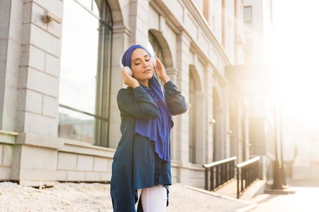 屋外のヘッドフォンを通して音楽を聴くヒジャーブを持つ少女 無料写真