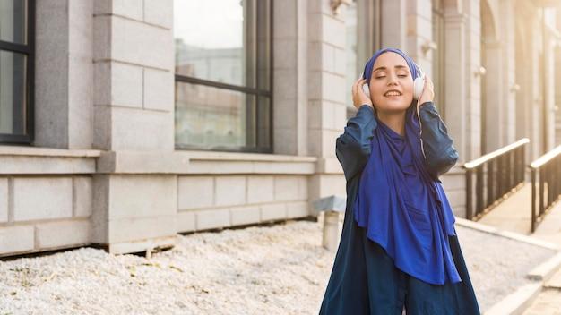 コピースペース付きのヘッドフォンで音楽を聴くヒジャーブを持つ少女 無料写真