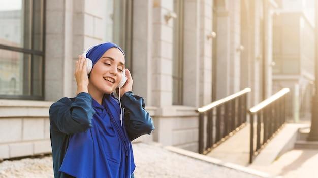 ヘッドフォンで音楽を聴くヒジャーブを持つ少女 無料写真