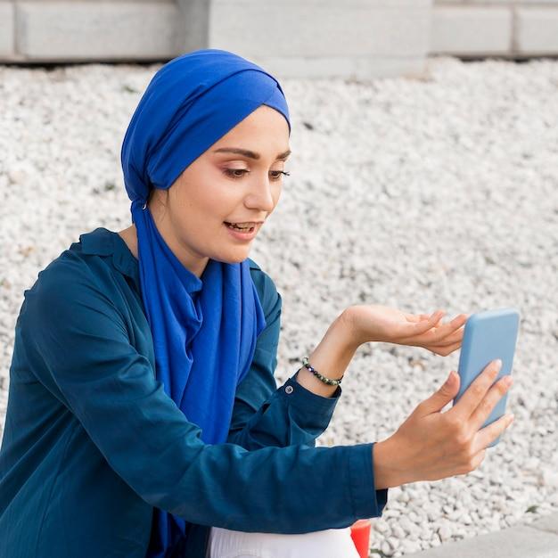 ヒジャーブのビデオ通話を持つ少女 無料写真