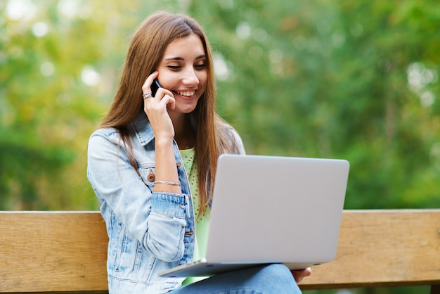 Girl with laptop in the park talking on the phone Premium Photo