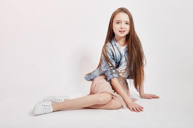 Girl with long hair in a denim jacket posing Premium Photo