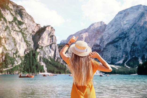 ドロミテのブラーイエス湖の上のドレスとカンカン帽の長い髪の少女。素晴らしい旅行。 Premium写真