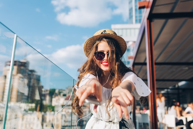 Girl with long hair  in sunglasses is listening to music through headphones on balcony. she wears a white dress, red lipstick and hat . she is stretching hands to the camera. buttom view. Free Photo
