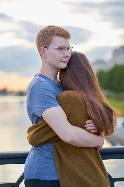 Girl with long thick dark hear embracing redhead boy on bridge, teen love Premium Photo