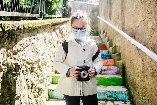 A girl with a mask goes sightseeing with a photo camera with colorful stairs Premium Photo